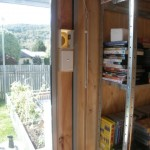 Plywood spacer placed in the sliding window with switch and air intake.
