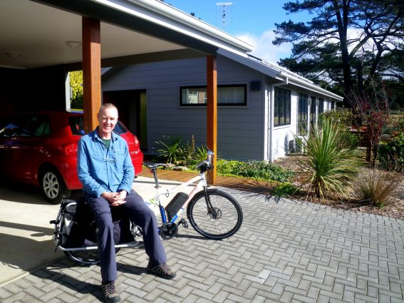 Glenn Robinson with his electric-assisted cargo bike in front of his energy positive house.