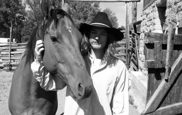 """Sam with his horse """"Brumby"""" by the old barn at Bones Brother's Ranch."""