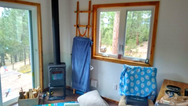 The cabin is primarily heated by this tiny little wood stove in the full-height living room