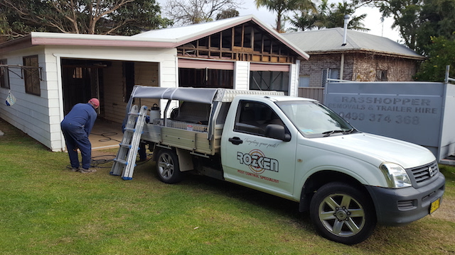 Pest controllers spraying for termites and cockroaches.