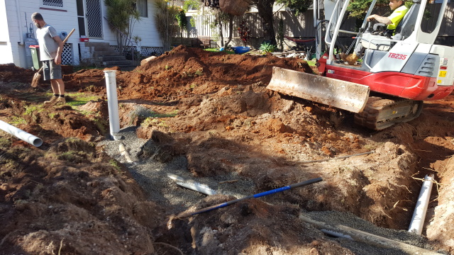 Tore up the back yard and installed electricity, phone, water, sewer and stormwater lines to connect to the existing services.