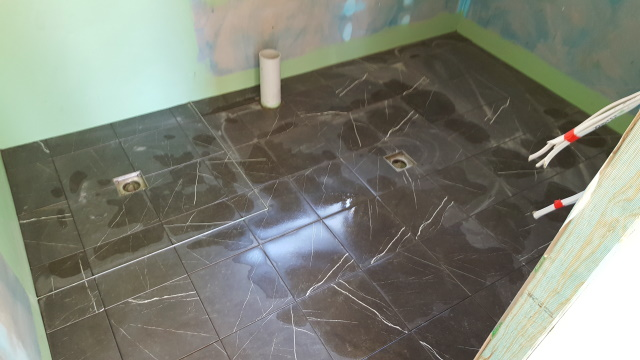 Waterproofing the bathroom and tiling the floor.